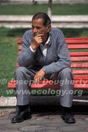 Man on park bench in colonial Andea city of Cuenca.