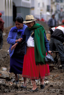 Indigenous women stepping through broken ground as workers repair the aging sewer system beneath the cobbled streets of Cuenca (