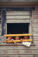Honduran children wave from the boarded window of their home.