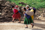 Indigenous women carrying children in the Andes