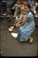 Philippine woman and children eating coconuts