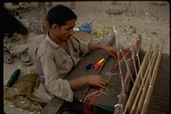 Man weaving wool