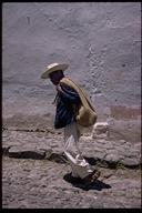 Man walking down cobblestone street